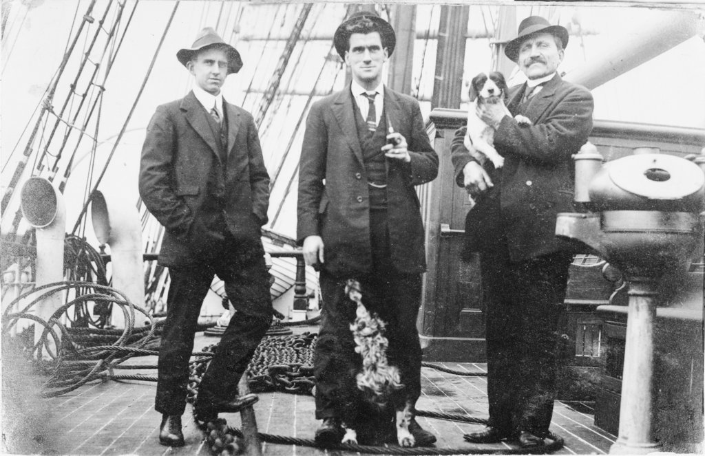 Detail of Second Officer, Captain H.J. Bray (with dog Ollie) and Chief Officer standing on deck, at Tacoma, USA by unknown